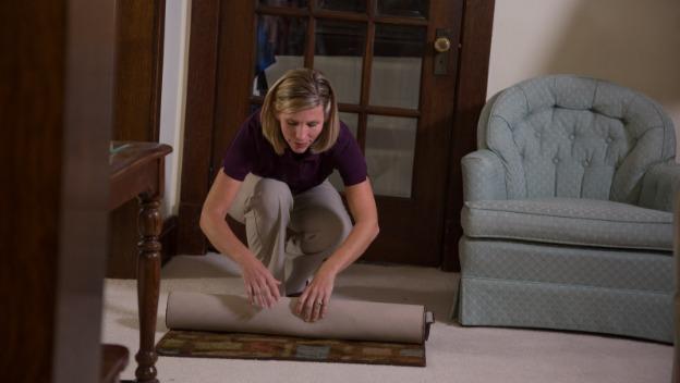Rotherham CAREGiver rolls up carpet to reduce falls risks