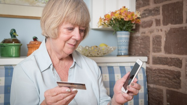 Rotherham woman with bank card on phone