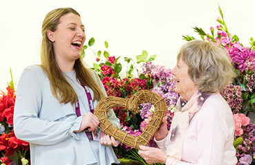 CAREGiver laughing with elderly lady holding a wooden heart