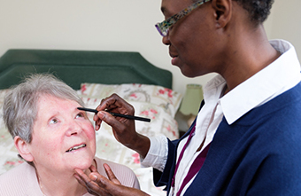 Elderly lady being assisted with her makeup by CAREGiver