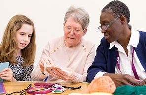 CareGiver crocheting with young girl and elderly lady