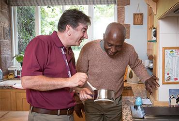 Eldery man and CAREGiver cooking food together