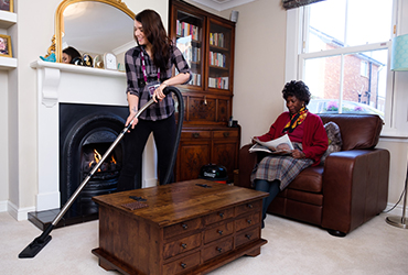 Elderly lady relaxing as CAREGiver helps her with hoovering her house