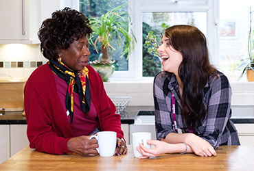 CAREGiver laughing with an elderly lady around a cup of tea