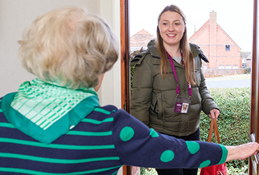 Elderly lady welcomes a Home Instead CAREGiver into home