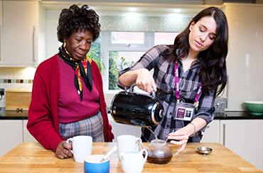 CAREGiver pouring tea with elderly lady in the kitchen