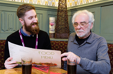 Male CAREgiver looking at food menu with elderly man