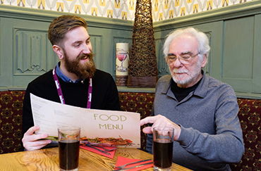 CAREGiver and elderly man looking at a menu together