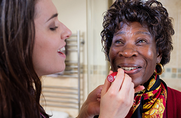 CAREGiver helping an elderly lady with applying lipgloss