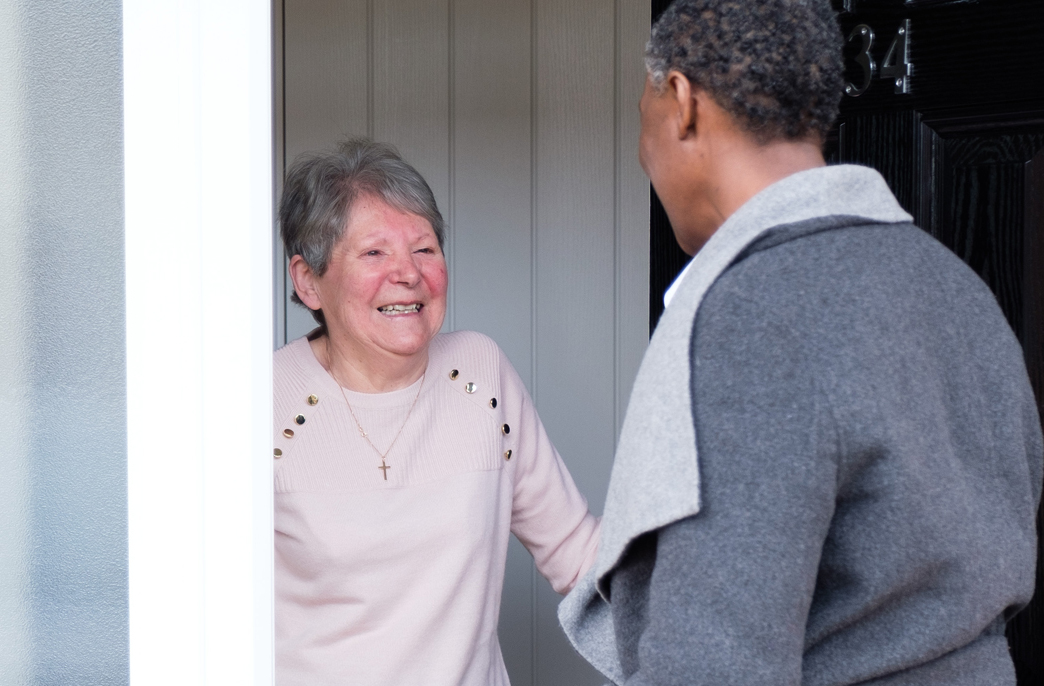 Elderly lady welcoming CAREGiver into home