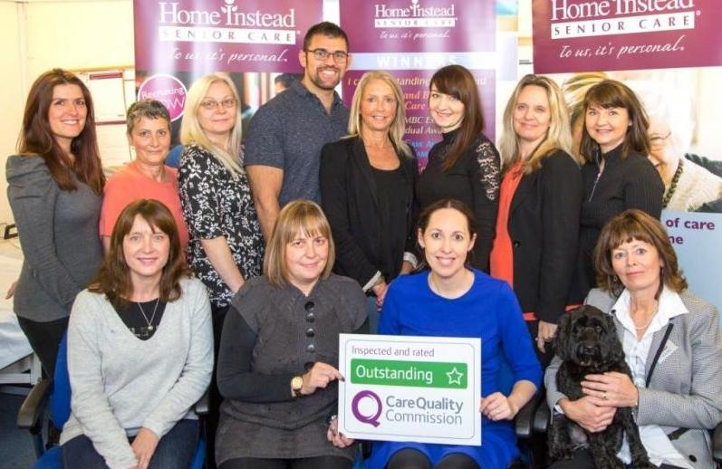 office group photo with CQC 'Outstanding' award