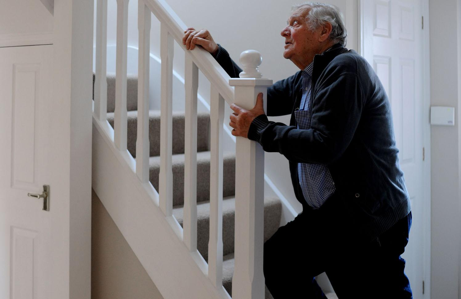 Elderly man struggles with stairs
