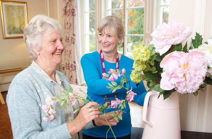 Elderly lady enjoying flower arranging with her CAREGiver