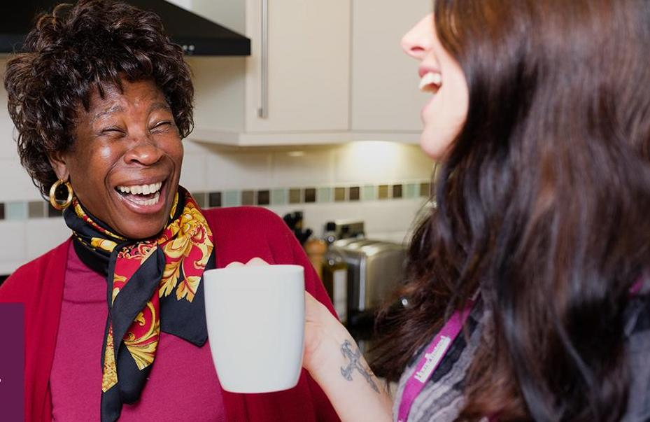 Client and CAREGiver laughing whilst drinking tea