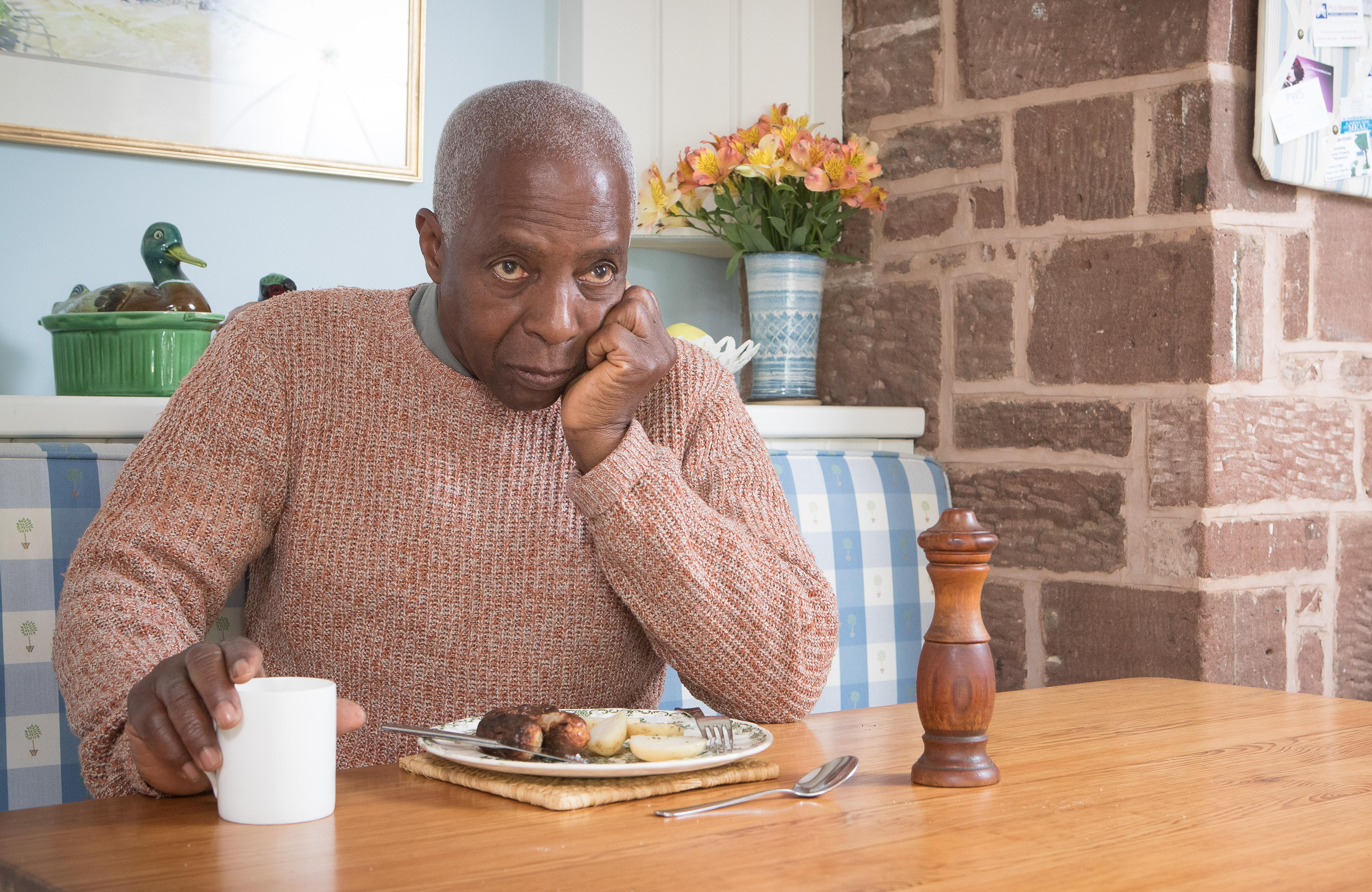 Lonely man eats dinner on his own.  Home Instead.