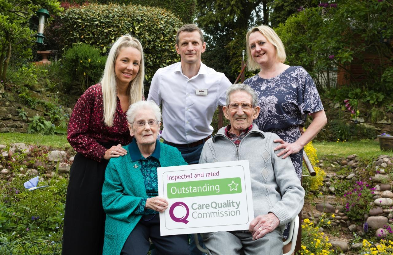 Photo of Home Instead Stourbridge team and clients with CQC Outstanding sign