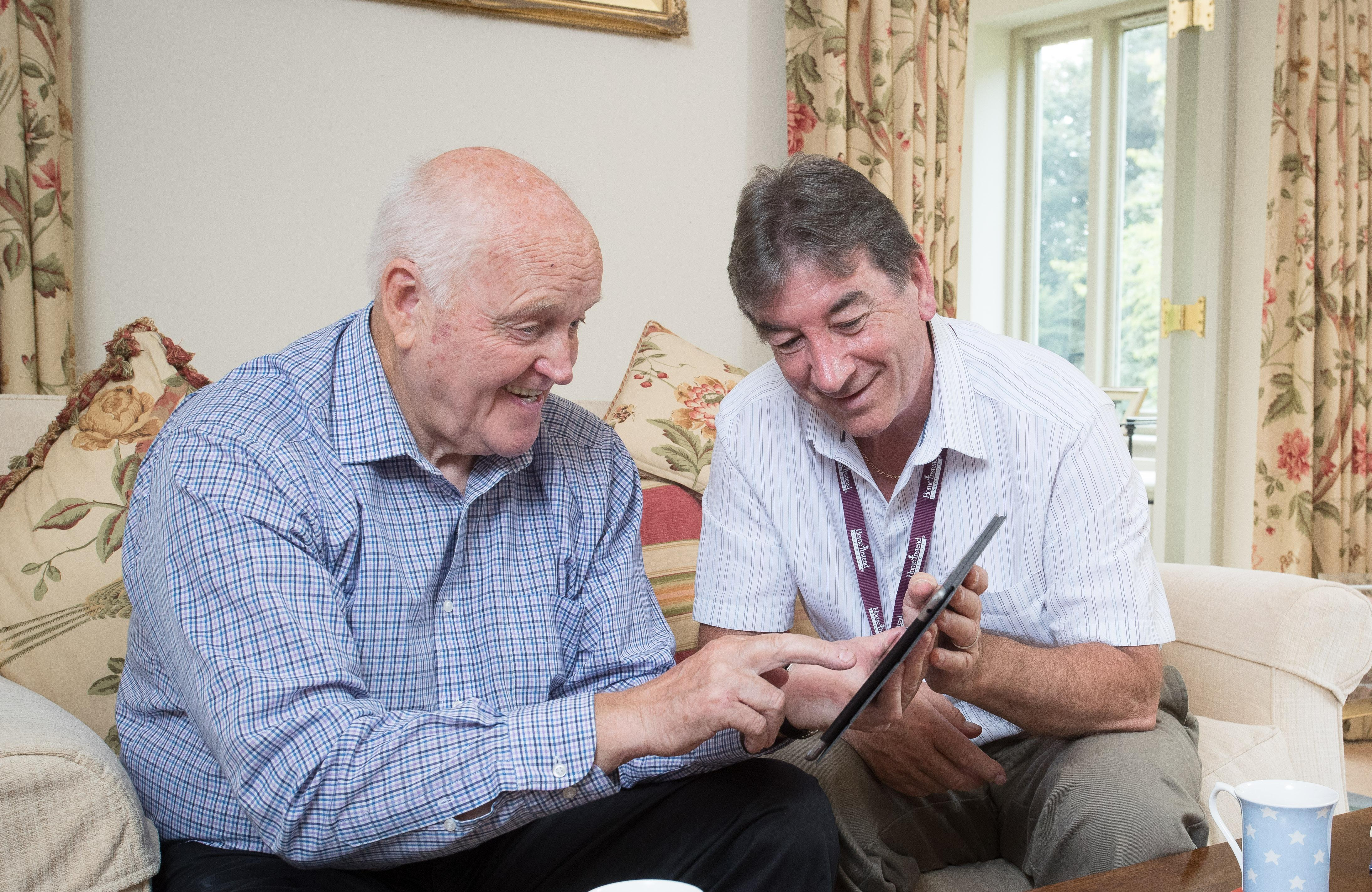 Photo of CAREGiver helping older man avoid online scams on iPad