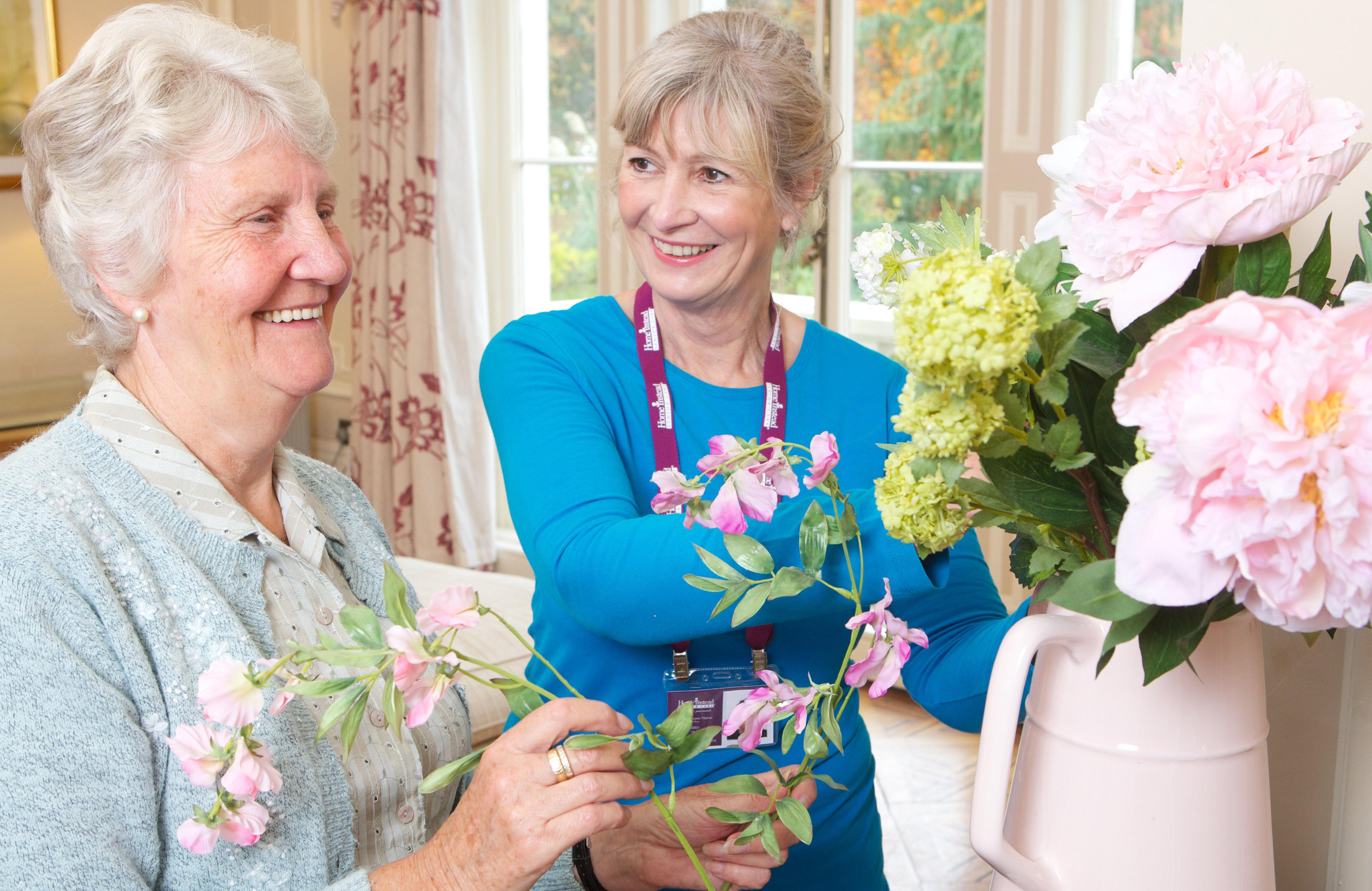 Caregiver helping elderly lady with flowers