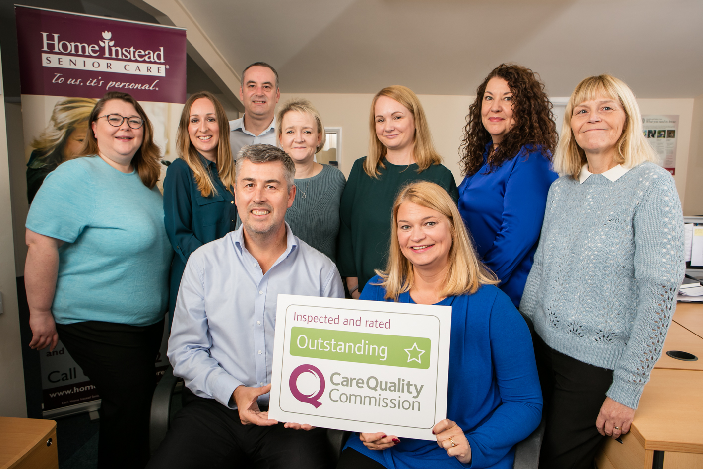 Home Instead Senior Care Brentwood, Billericay and Upminster office team holding their CQC Outstanding rating